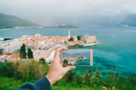 Hand holds a phone with a photo on display. The old town can be seen in the distance