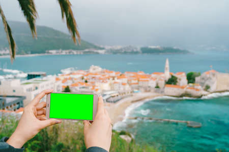 Smartphone in hands with a blank screen on the background of Budva
