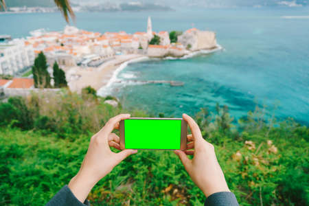 Hands are holding a smartphone with a blank screen. In the distance is the old town. Montenegro