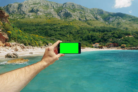 Mans hand holds a smartphone with a blank screen on a background of green mountains and blue sea