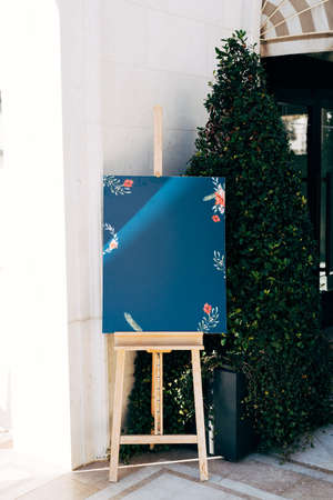 Wooden easel stands on a stand against the backdrop of a building and a beautiful green spruce