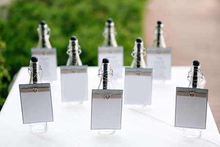 Sealed bottles with blank signs stand on a table covered with a white tablecloth