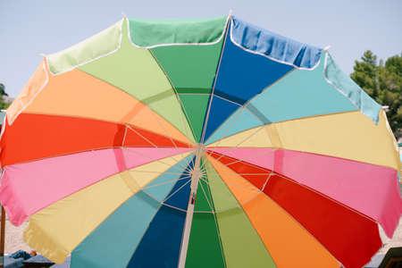 Opened bright colored sun umbrella on a blue sky background