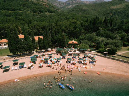 Top view of the royal beach in Przno. Colored sun umbrellas stand on the sand, people swim in the sea and sail in boats