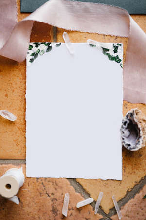 A blank white letterhead lies on a stone tile framed by a ribbon, a shell and a skein of thread Imagens