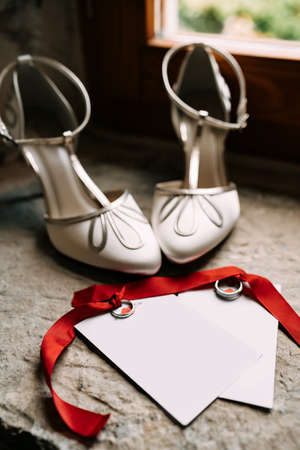 Wedding rings tied with red ribbons lie on blank postcards with ornaments next to white high-heeled shoes against the background of a stone window sill Imagens