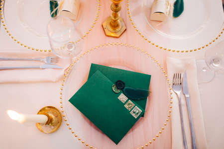 Blank green envelopes with stamps lie on a transparent plate on a set table. A lighted candle is burning on the left. Top view Imagens