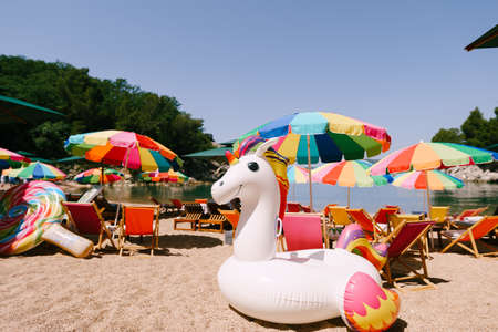 Inflatable white unicorn on the royal beach in Przno against the backdrop of green trees