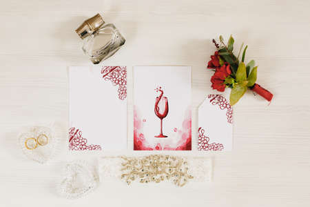 Wedding rings lie in a heart-shaped crystal box on the table. Nearby lies a small bouquet of roses, perfume and a watercolor painting with a picture glass of wine Imagens