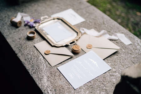 On the stone slab are wax-sealed envelopes, a metal tray, ribbons and postcards Imagens