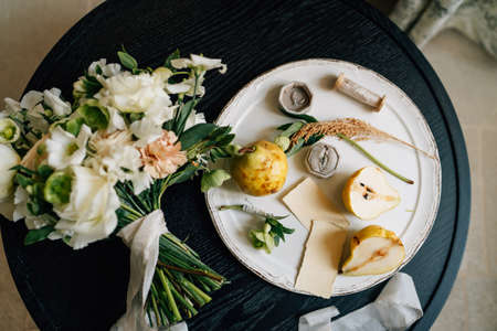 Wedding ring lies in a box on a white plate next to pears and green twigs. A plate with a bouquet of flowers tied with a ribbon stands on a wooden table