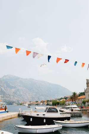 White boats stand on the pier of the Kotor bay against the backdrop of a beautiful old town