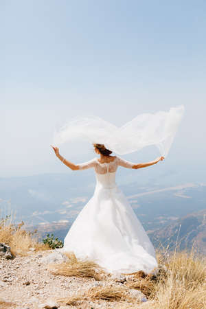 An elegant bride stands on Mount Lovcen above the Bay of Kotor with her arms outstretched, the wind wind will blow a veil over her