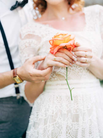 Groom holds the brides hand in a white lace dress with a rose in her hands. Close up