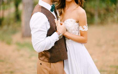 Stylish newlyweds posing hugging on the background of green nature Imagens