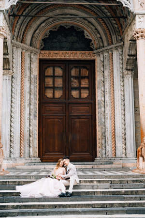Entrance to the Basilica of Santa Maria Maggiore, Rome. Newlyweds are sitting on the steps embracing Imagens