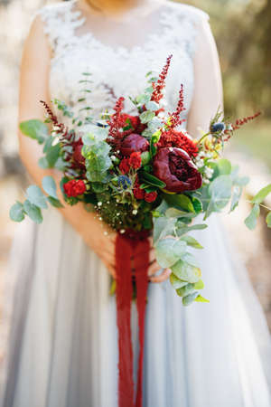 A bride in a pale gray wedding dress holds a bouquet with red peonies, astilba, roses and eringium and red long ribbons, close-up