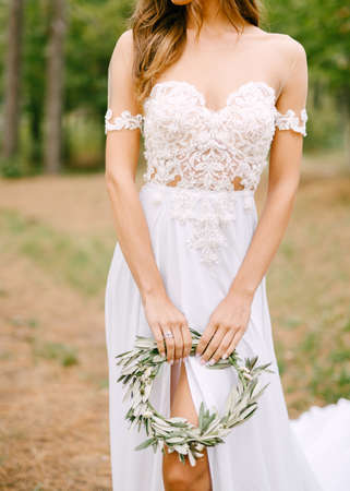 Stylish bride in a lace embroided dress with a cutout on the leg holding a wreath of olive branches