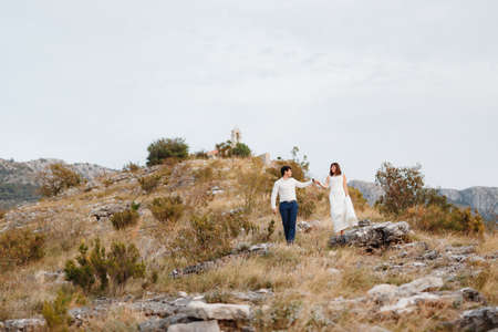 Bride and groom go down the mountainside. Groom holds brides hand