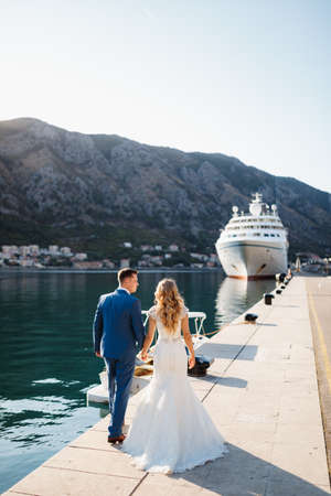 The bride and groom are walking holding hands along the pier near white tourist liner, back view Imagens