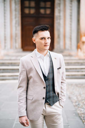 Serious groom in a beige suit holds his hand in his pants pocket on the background of an old door. Bergamo, Italy