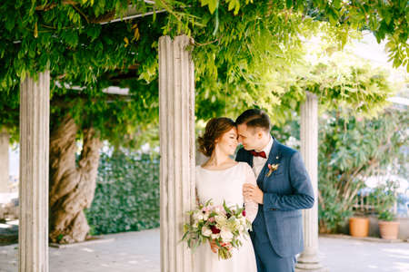 Smiling groom hugs the brides shoulders against the background of columns in a green garden Imagens