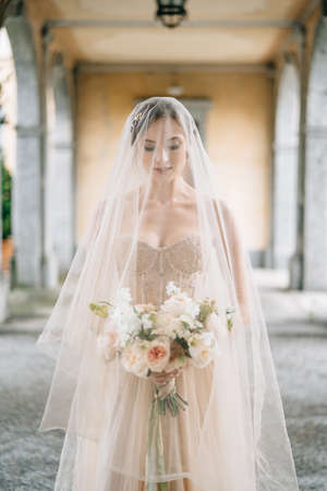 Bride in a wedding dress and a veil with a bouquet stands with her eyes downcast on an old terrace with columns. Lake Como