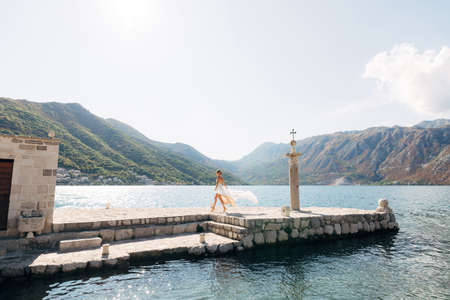 A bride walks along a stone pier next to an old column in the Bay of Kotor, her skirt flutters in the wind
