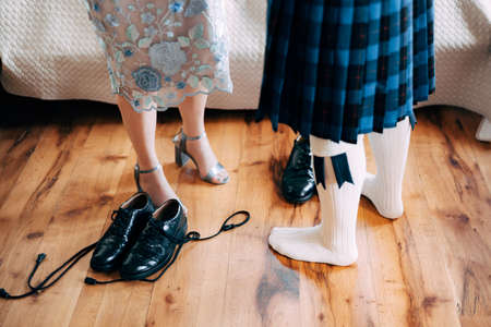 Scottish wedding preparations. Man in a kilt stands next to woman in a skirt with high-heeled shoes. There are shoes with long laces on the floor
