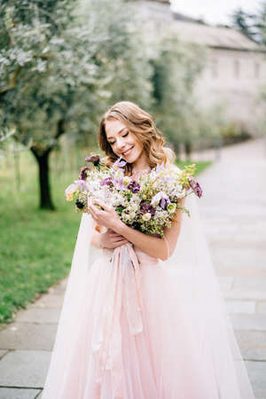 Bride in a beautiful pink dress smiling holds a bouquet of flowers in her hands on the background of an olive grove Imagens