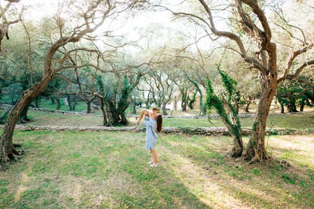 Mom throws up the child, kisses and plays with him among the trees in the olive grove