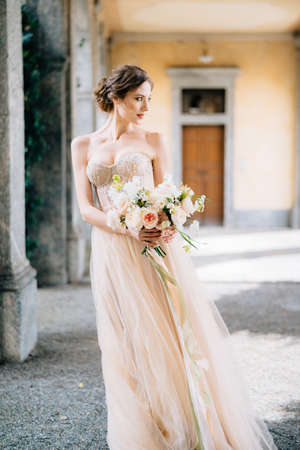 Bride in a beautiful dress with a bouquet of pink flowers stands in the vaulted hall with her head turned. Lake Como, Italy