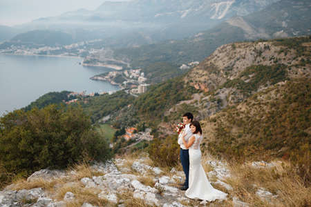 Newlyweds hug on the background of a panorama of the city of Budva, mountains and the sea