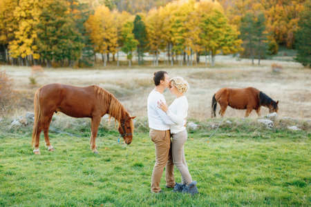 Man hugs and kisses woman on the forehead against the background of grazing horses in the autumn forest