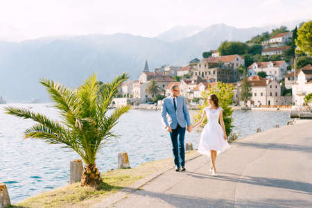 Smiling bride and groom walk along the road holding hands against the background of buildings of the city of Perast in Montenegro Imagens