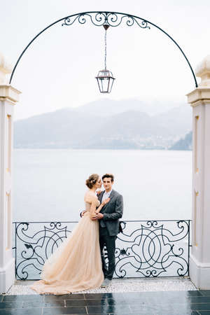 Newlyweds hug and almost kiss under an old arch against the backdrop of Lake Como