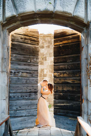 Bride hugs groom while standing behind the open wooden gate of the castle Imagens