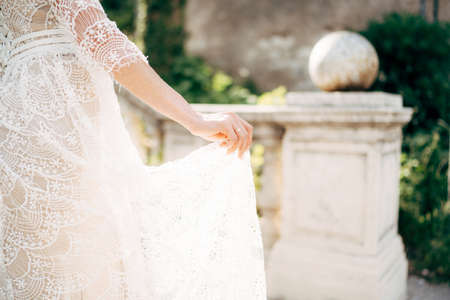 Bride holds with her fingers the floor of a white lace wedding dress on the background of the columns in the garden Banco de Imagens