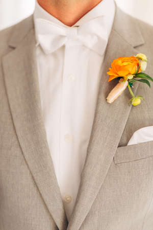 The groom in a gray suit with a white bow tie and a boutonniere with orange flowers in a hotel room, close-up