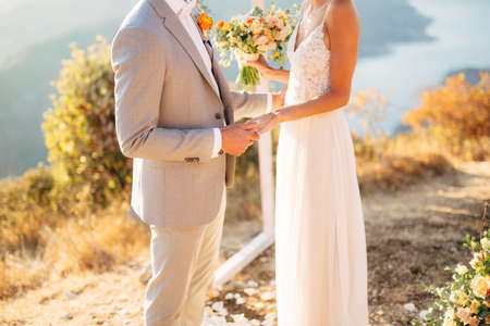 The bride and groom are standing on Mount Lovcen near the wedding arch and holding hands