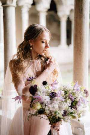 Bride in a beautiful pink dress holds a bouquet of wildflowers in her hand against the background of an old building in Lake Como