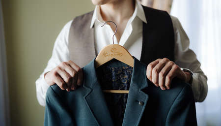 Groom in a white shirt and vest holds a jacket on a hanger Banco de Imagens