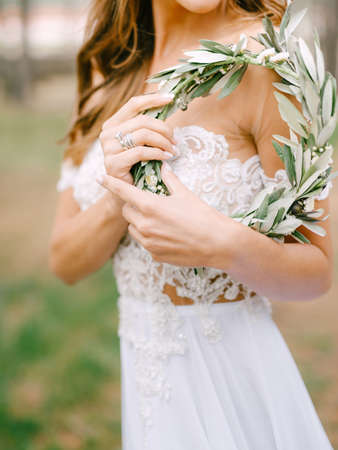 Beautiful bride in a white embroidered dress stands sideways and holds a wreath of green olive branches in her hands