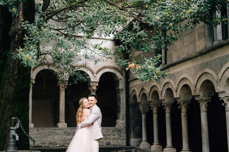 Groom hugs smiling bride standing in the green garden against the background of an old villa with columns on Lake Como, Italy Banco de Imagens
