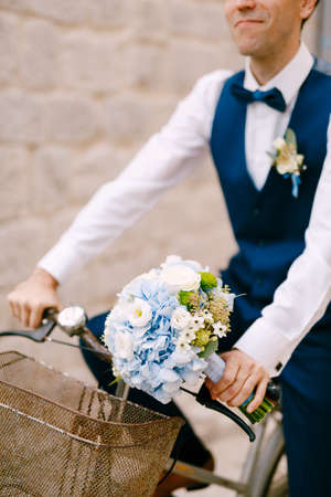 Smiling groom with a bouquet of beautiful flowers rides a bicycle
