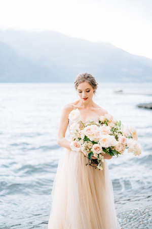 Pensive bride with a bouquet of flowers stands on the shore of Lake Como against a background of mountains
