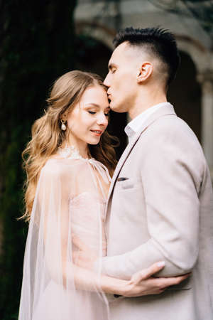 Groom kisses the forehead of smiling bride in a beautiful pink dress