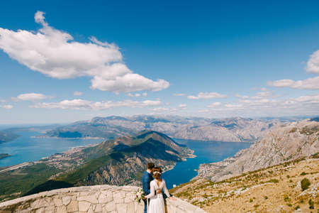 Groom and bride are embracing and looking at the Kotor Bay. Beautiful view from mountains of Montenegro