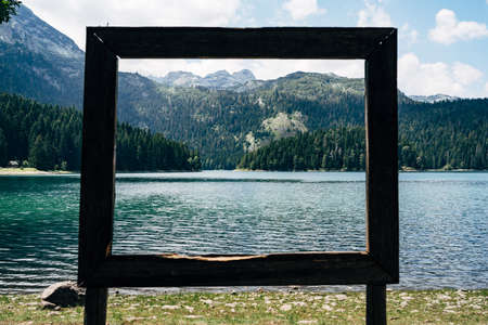 Picturesque view of the lake through the wooden frame Banco de Imagens
