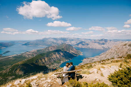 Bride and groom are sitting on a bench and looking at the Kotor bay. Excellent view from the mountains of Montenegro